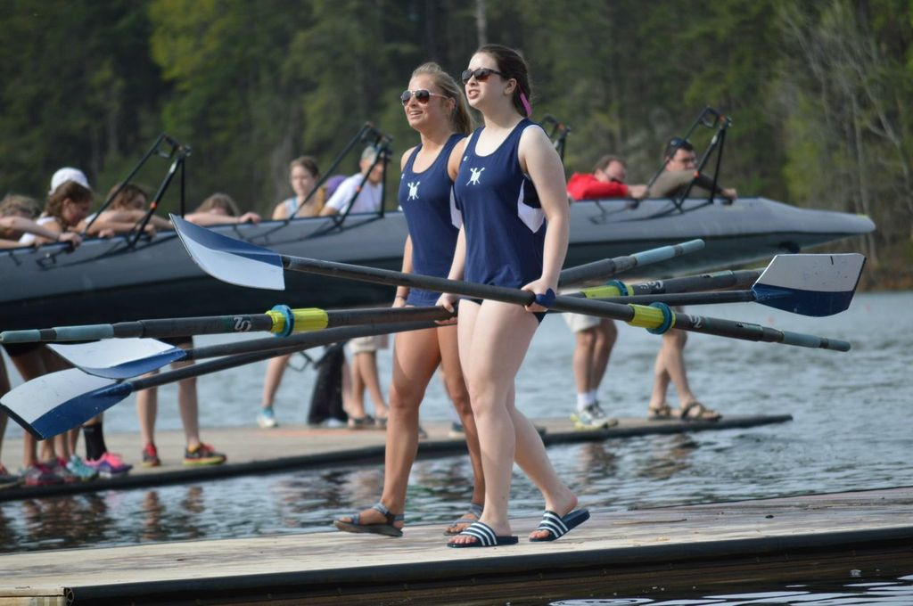 Addy Millsap and Victoria Goldin carry their oars to shore after racing in the women's novice eights event at Clemson Sprints.