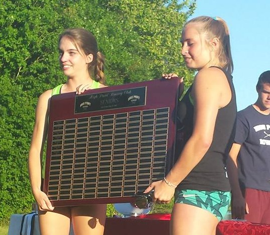 High Point Senior rowers Kim Pollard and Addy Millsap present the senior gift to the team, a plaque commemorating each senior of the team since the club was formed.